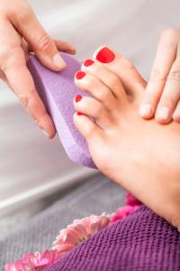 Frau mit Pediküre in einem Beautysalon auf einem Handtuch